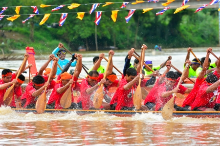 CHUMPHON, THAILAND-OCT 20  Unidentified rowers in Climbing Bows toward Snatching a Flag native Thai long boats compete during King s cup Native Long Boat Race Championship on Oct 20, 2013 in Chumphon, Thailand