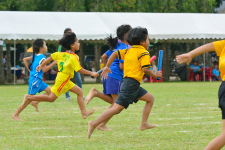 CHUMPHON - DECEMBER 20   Unidentified children doing a teamwork run racing at Kindergarten sport day on 20 December, 2013 in Chumchonwatkhanngoe n school, Chumphon, Thailand