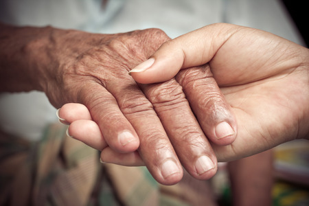 Senior and young holding hands photo