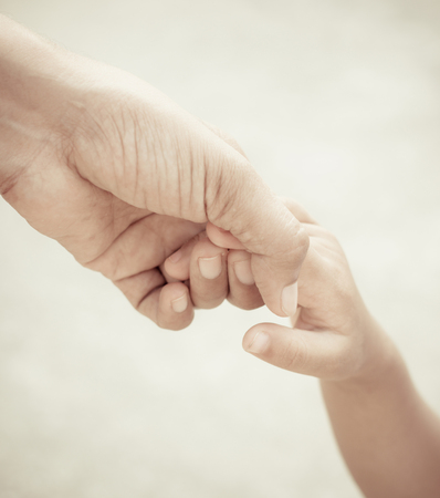aiding: Mother holding a hand of child Stock Photo