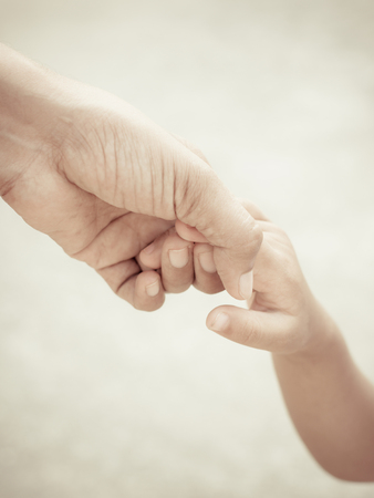 Mother holding a hand of child photo