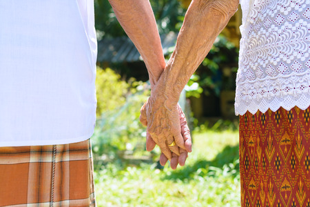 asian elderly couple holding hands
