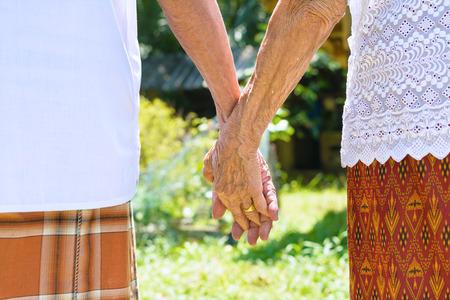 asian elderly couple holding hands