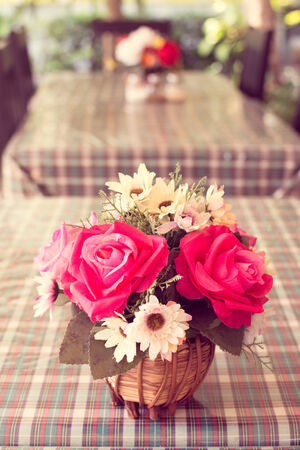 beautiful artificial roses on table with retro filter effect photo