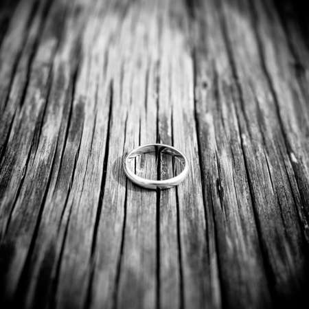 black and white   wedding or engagement ring on wood photo