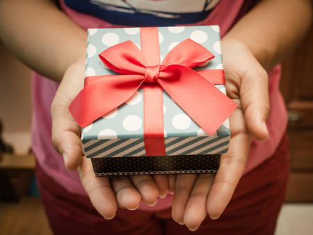 red hand: Woman holding a gift box in a gesture of giving Stock Photo