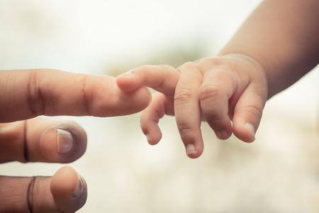 Närbild av mor och barn händer med retro effekt Stockfoto