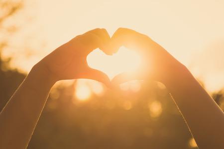 mãos que formam uma forma do coração no por do sol