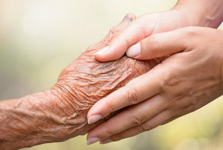 loving hands: Senior and young holding hands Stock Photo