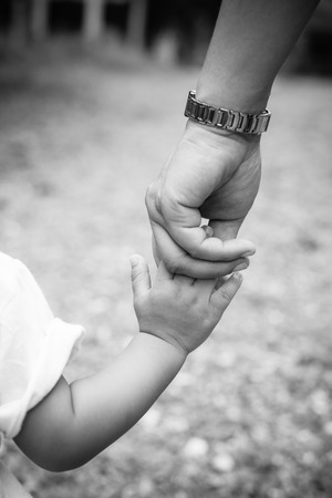 feel affection: Mother holding a hand of child with black and white effect