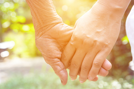Senior and young holding hands and color tone effect
