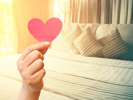 bed sheet: vintage bed and paper heart in hand with color tone effect