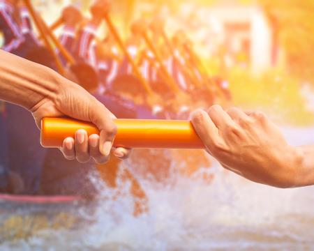 handen die een relaisbaton overlaten op rowing team achtergrond en kleur tone effect.