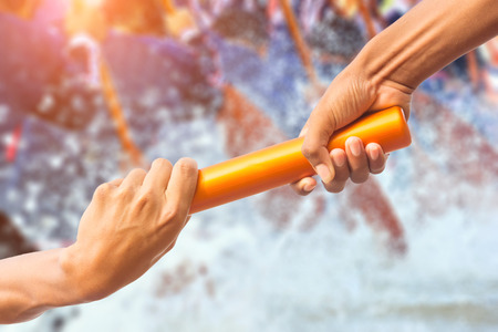hands passing a relay baton on rowing team background and color tone effect. Stock Photo