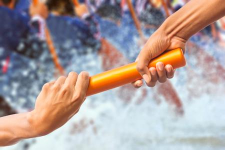 manos que pasan un bastón del relais en fondo del equipo del rowing y efecto del tono del color.
