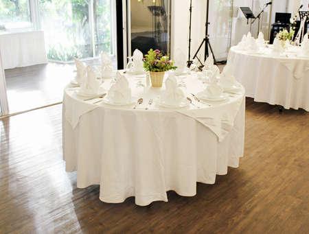 Ronde tafel met eettafel van witte stof met buitenachtergrond