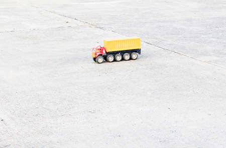 Plastic toy truck with bright colors on the empty concrete floor.