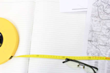 White Note on the desk with long yellow measuring tape. Eye glasses with maps