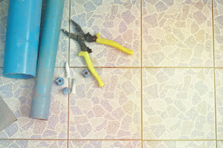 Pvc hose pliers on the bathroom floor tiles.