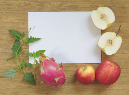 Dragon fruit, purple, yellow wheelbarrow Yellow-red apples on white paper, leaves, wood background, brown pattern