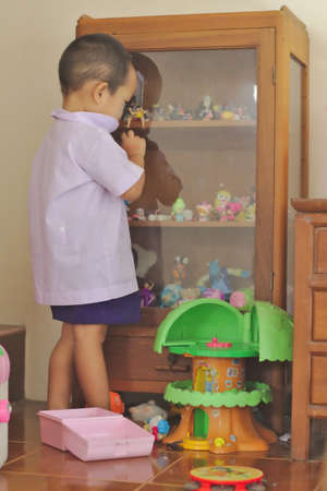 Kindergarten students White school uniform Look at toys in the toy showcase.Baby toys spread all over the floor of the room. Sajtókép