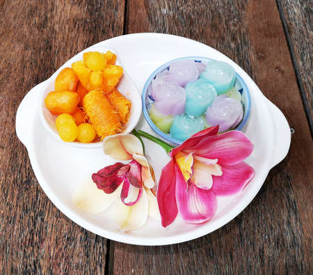 Angel hair or Egg threads, Thong yot or Gold egg-yolks drops, Thong yip or Pinched gold egg yolk, Met khanun or Jackfruit seed in white bowl, and Khanom Chan or Thai layer dessert blue bowl are the auspicious traditional Thai desserts made from egg yolks, flour and sugar. Reklamní fotografie