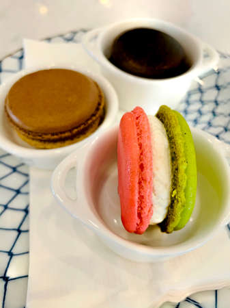 Vertical macro photography of sweet green tea and raspberries macaron in a small white cup and another flavors with full depth of field on white napkins.
