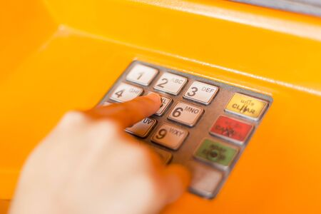 the entering: Hand entering PIN numbers on ATM bank machine