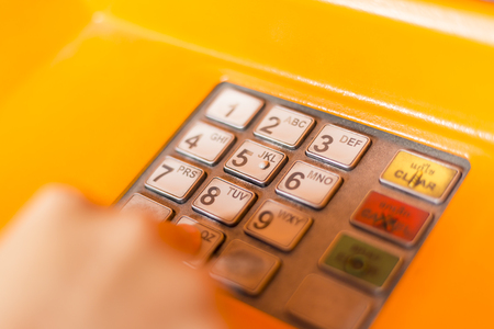 automatic teller machine: Hand entering PIN numbers on ATM bank machine