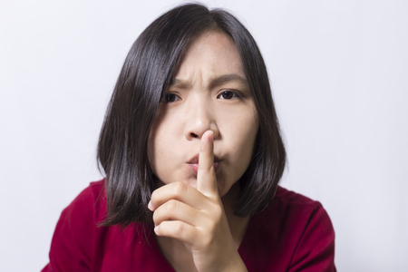Woman saying hush be quiet on white background.