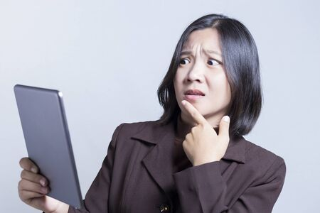 negative thinking: Businesswoman Use Tablet and Thinking: Negative Thinking Stock Photo