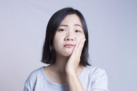 dolor de muela: La mujer joven está teniendo dolor de muelas