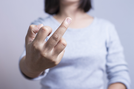 fuck: Bad woman is showing fuck off with the middle finger