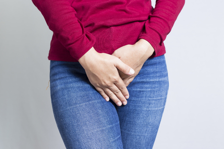 urination: Woman with Hands Holding her Crotch Isolated in a White Background