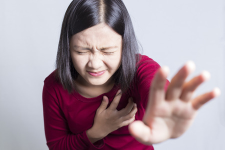 heart hands: Woman having a pain in the heart area, isolated in white background