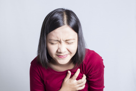woman chest: Woman having a pain in the heart area, isolated in white background