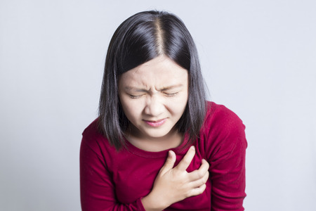 hand on chest: Woman having a pain in the heart area, isolated in white background