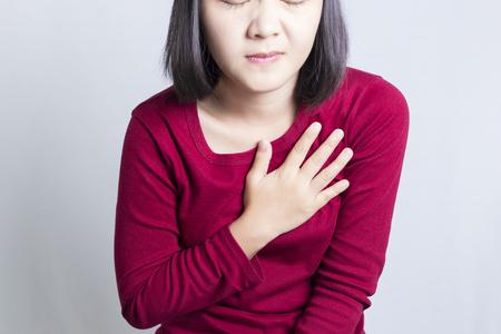 dolor en el pecho: Mujer que tiene un dolor en el �rea del coraz�n, aislado en fondo blanco