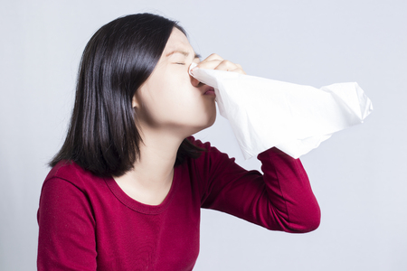 snot: Sick Woman Sneezing in to Tissue Paper Stock Photo