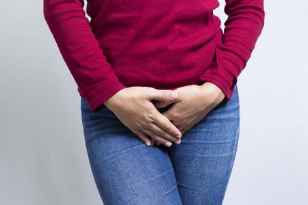 sexuel: Femme avec les mains tenant son entrejambe isolé dans un fond blanc