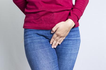 Femme avec les mains tenant son entrejambe isolé dans un fond blanc Banque d'images - 48105418