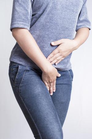 cervicales: Mujer con las manos sosteniendo su entrepierna aislada en un fondo blanco Foto de archivo