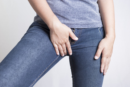 crotch: Woman with Hands Holding her Crotch Isolated in a White Background