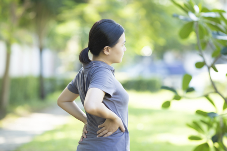 spinal manipulation: Woman with Pain in Her Lower Back Stock Photo