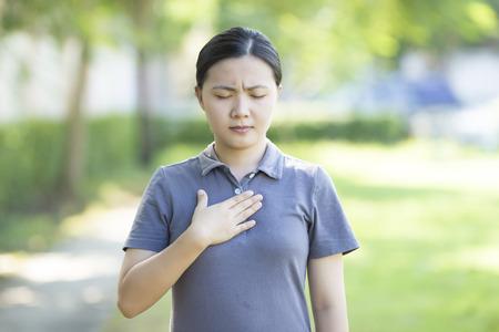 dolor de pecho: Dolor en el pecho de la mujer en el parque Foto de archivo