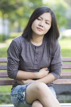 stomachache: Woman has Stomachache at Park