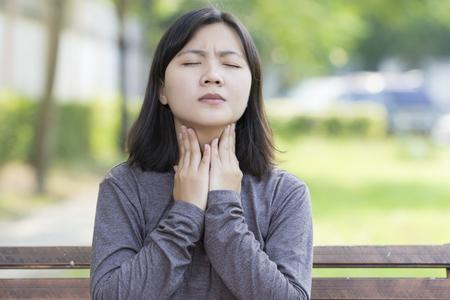 女性が公園で喉の痛みを持っています。