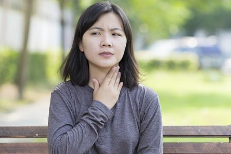 여자는 공원에서 목의 통증이있다