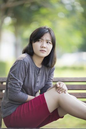 stomachache: Woman Stomachache at Park Stock Photo