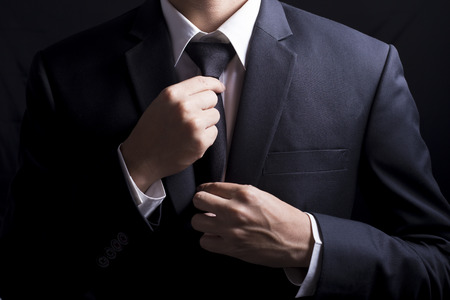 suit tie: Businessman Adjust Necktie his Suit Stock Photo